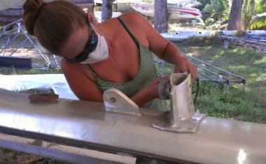 Amanda using a grinder & polishing pad to touch up the mast
