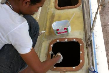 "Smearing ""hairy"" epoxy mud into the hatch mounting holes"