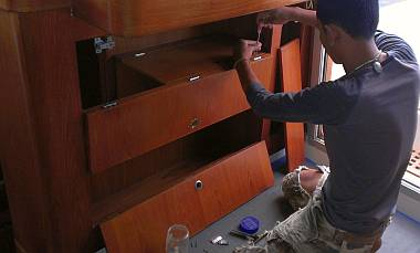 Baw installing the newly varnished nav-desk cupboard doors