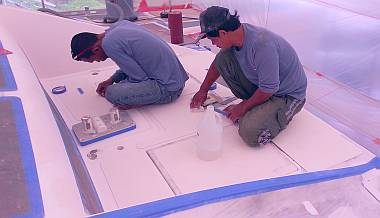 Baw and Pla finalizing gelcoat preparations on the foredeck