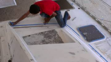 Baw masking the starboard foredeck with blue-tape