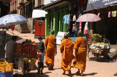 Monks on cobbled streets walking past fruit vendors
