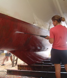 Amanda having fun cleaning the hull with the borrowed power sprayer..