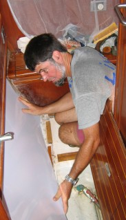 Jon fits a new formica panel in our cabin after Sue removed the old liner.