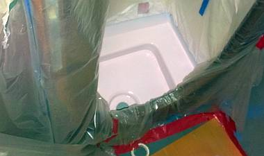 One of the sprayed shower pans, all masked in plastic