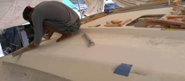 Heru smoothing off the new filler on the starboard cabin-top