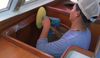 Heru polishing the new gloss polyurethane trim in the salon