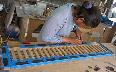 Houa gluing rubber pads to the bottom of the teak grate