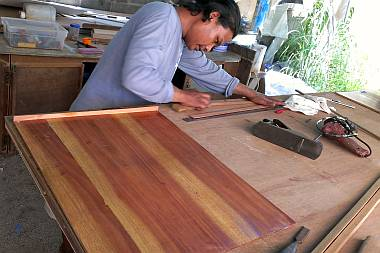 "Houa working on one of our ""Galapagos teak"" shelves"