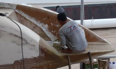 Lek epoxying the first layer of fiberglass onto our starboard wall