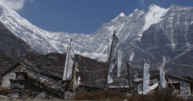 Prayer flags and mani walls under the towering peaks