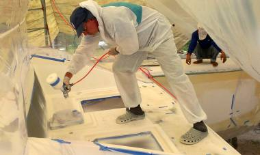 Mike spraying the foredeck inside a plastic tent of masking