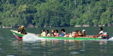 Papuan villagers wave from their long boat